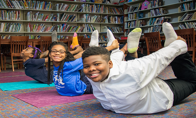 Three students at College Hill Fundamental Academy Afterschool Club practicing yoga.