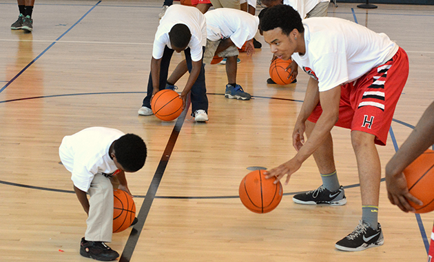 A teen helping a younger student work on his dribbling technique at the KISR! Basketball Clinic and Tournament.